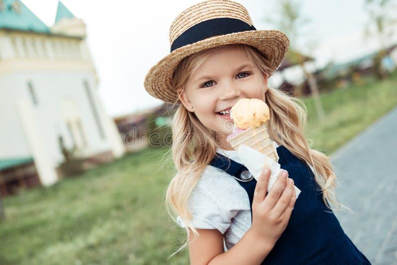 πορτρέτο του χαμογελώντας μικρού κοριτσιού με το διαθέσιμο κοίταγμα παγωτού στοκ φωτογραφία με δικαίωμα ελεύθερης χρήσης