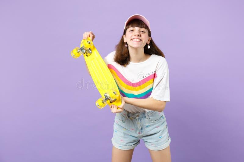 Πορτρέτο του χαμογελώντας όμορφου κοριτσιού εφήβων στα ζωηρά ενδύματα που κρατά κίτρινο skateboard απομονωμένο στον ιώδη τοίχο κρ στοκ φωτογραφία με δικαίωμα ελεύθερης χρήσης
