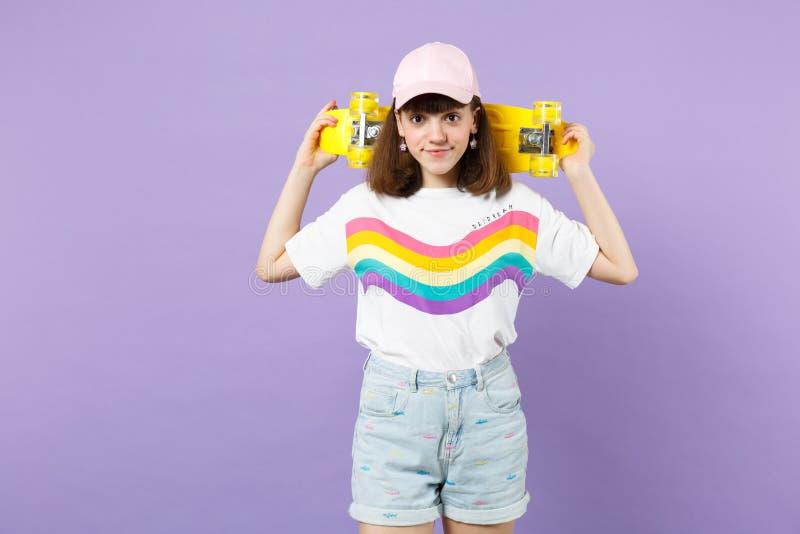 Πορτρέτο του χαμογελώντας όμορφου κοριτσιού εφήβων στα ζωηρά ενδύματα που κρατά κίτρινο skateboard απομονωμένο στον ιώδη τοίχο κρ στοκ εικόνα με δικαίωμα ελεύθερης χρήσης