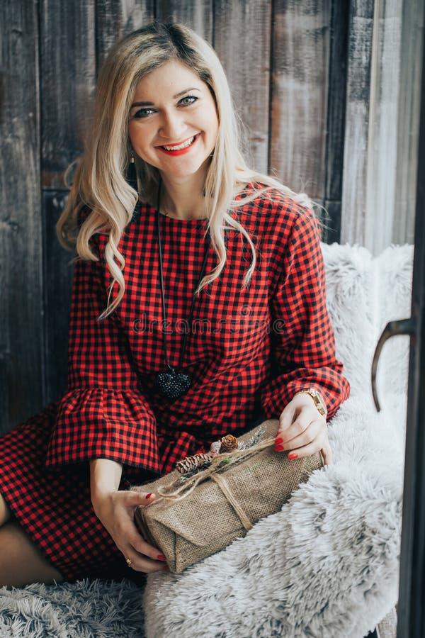 Πορτρέτο του χαμογελώντας όμορφου κοριτσιού με την ξανθή σγουρή τρίχα και το έκπληκτο χαμόγελο που κρατούν τα χέρια της κοντά στο στοκ εικόνα
