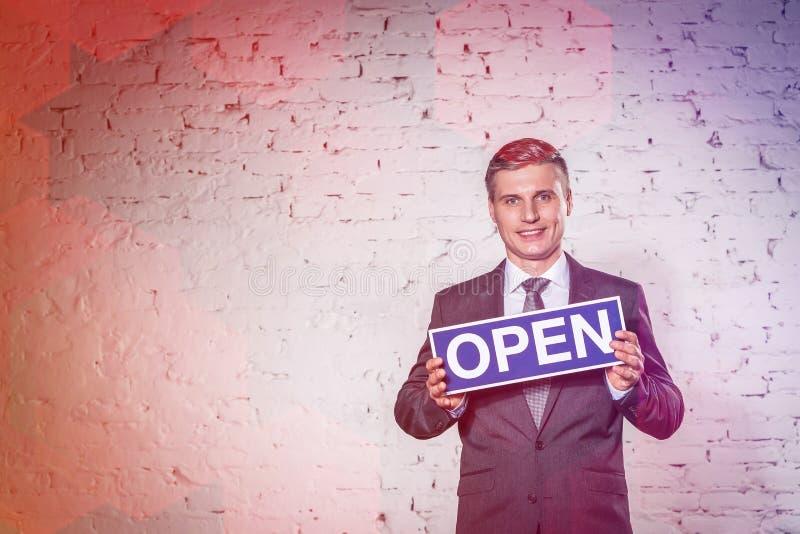 Πορτρέτο του χαμογελώντας ώριμου επιχειρηματία που διοργανώνει το ανοικτό σημάδι ενάντια στο τουβλότοιχο στο γραφείο στοκ φωτογραφία με δικαίωμα ελεύθερης χρήσης