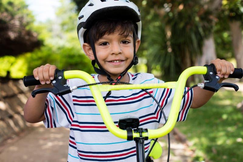 Πορτρέτο του χαμογελώντας αγοριού που στέκεται με το ποδήλατο στο πάρκο στοκ εικόνα