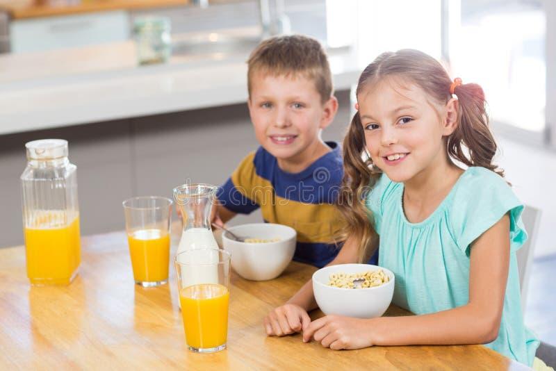 Πορτρέτο του χαμογελώντας αμφιθαλή που έχει τα δημητριακά προγευμάτων στην κουζίνα στοκ εικόνες με δικαίωμα ελεύθερης χρήσης
