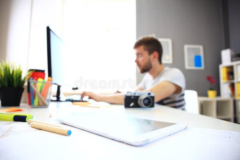 Πορτρέτο του χαμογελώντας αρσενικού συντάκτη φωτογραφιών που χρησιμοποιεί τον υπολογιστή στοκ φωτογραφία