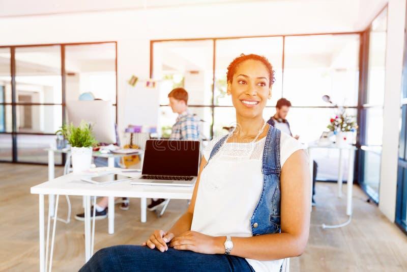 Πορτρέτο του χαμογελώντας αφροαμερικανού εργαζομένου γραφείων στο offfice με τους συναδέλφους της στοκ φωτογραφία