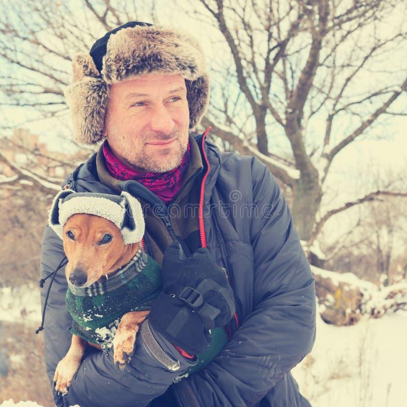 Πορτρέτο του χαμογελώντας γενειοφόρου ατόμου και του μικρού σκυλιού στοκ εικόνες με δικαίωμα ελεύθερης χρήσης