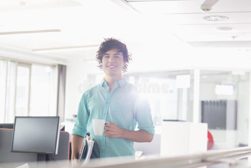 Πορτρέτο του χαμογελώντας επιχειρηματία που έχει τον καφέ στο δημιουργικό γραφείο στοκ φωτογραφία με δικαίωμα ελεύθερης χρήσης