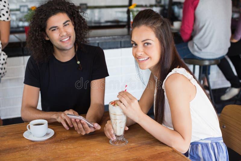 Πορτρέτο του χαμογελώντας ζεύγους που χρησιμοποιεί το κινητό τηλέφωνο ενώ έχοντας τα ποτά στο εστιατόριο στοκ εικόνα