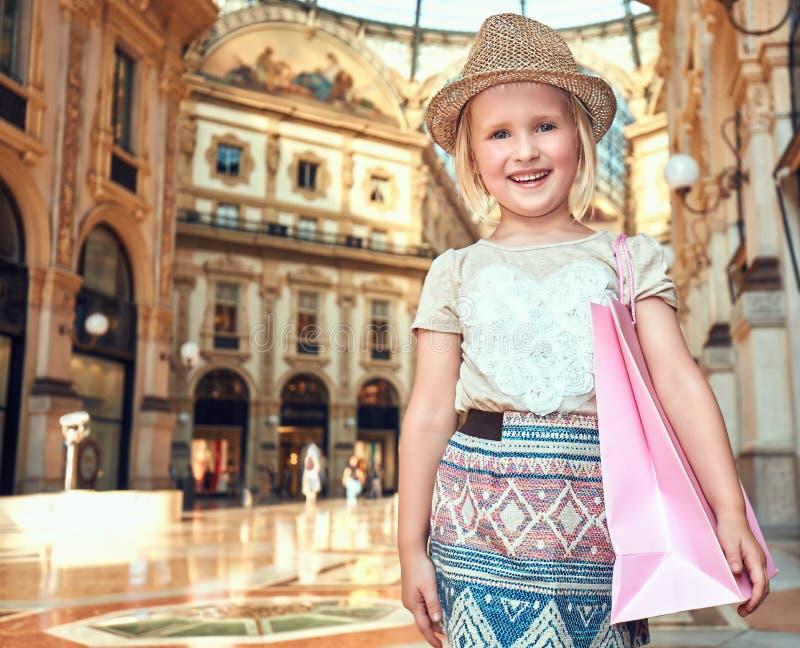 Πορτρέτο του χαμογελώντας κοριτσιού μόδας με την τσάντα αγορών σε Galleria στοκ εικόνες