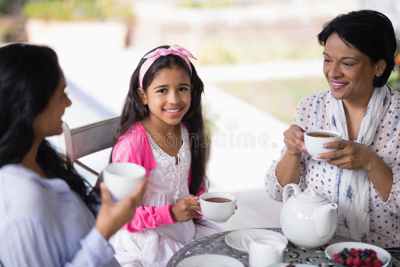 Πορτρέτο του χαμογελώντας κοριτσιού που έχει το πρόγευμα με τη μητέρα και τη γιαγιά στοκ εικόνα
