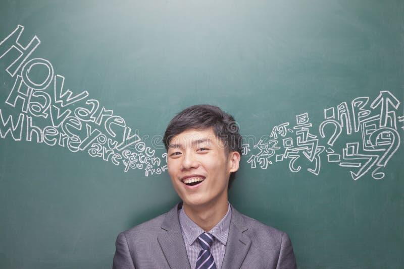 Πορτρέτο του χαμογελώντας νέου επιχειρηματία μπροστά από το μαύρο πίνακα με το κινεζικό και αγγλικό χειρόγραφο που προέρχεται από  στοκ φωτογραφίες