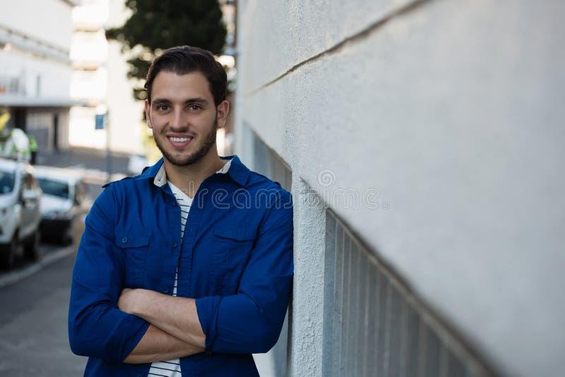 Πορτρέτο του χαμογελώντας νεαρού άνδρα με τα όπλα που διασχίζονται στοκ φωτογραφία με δικαίωμα ελεύθερης χρήσης
