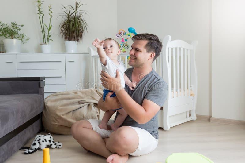 Πορτρέτο του χαμογελώντας πατέρα που έχει τη διασκέδαση με το πάτωμα μωρών του στο flo στοκ εικόνα με δικαίωμα ελεύθερης χρήσης