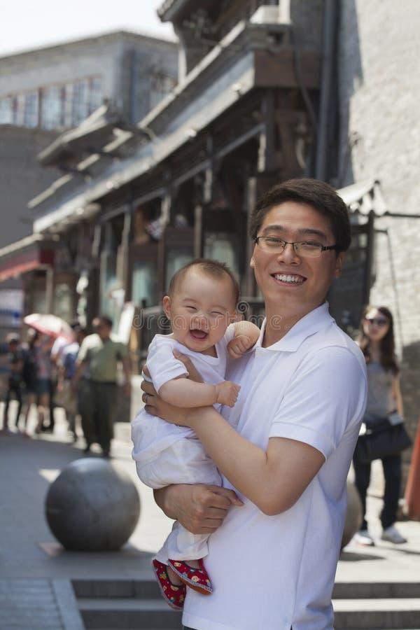 Πορτρέτο του χαμογελώντας πατέρα που κρατά τον ευτυχή γιο μωρών του, υπαίθρια Πεκίνο στοκ εικόνες με δικαίωμα ελεύθερης χρήσης