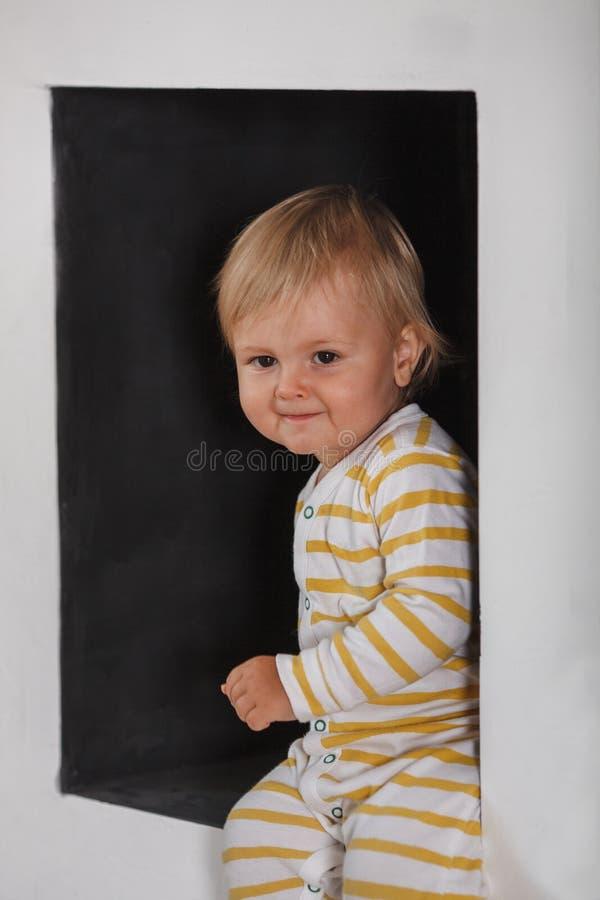 Πορτρέτο του χαμογελώντας χαριτωμένου μικρού παιδιού στη μαύρη θέση τοίχων στοκ φωτογραφία με δικαίωμα ελεύθερης χρήσης