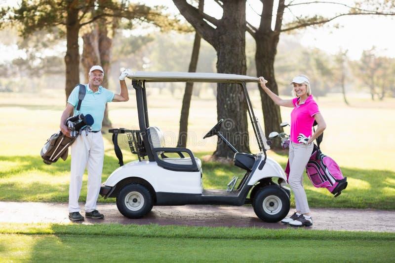 Πορτρέτο του χαμογελώντας ώριμου ζεύγους παικτών γκολφ στοκ εικόνα με δικαίωμα ελεύθερης χρήσης
