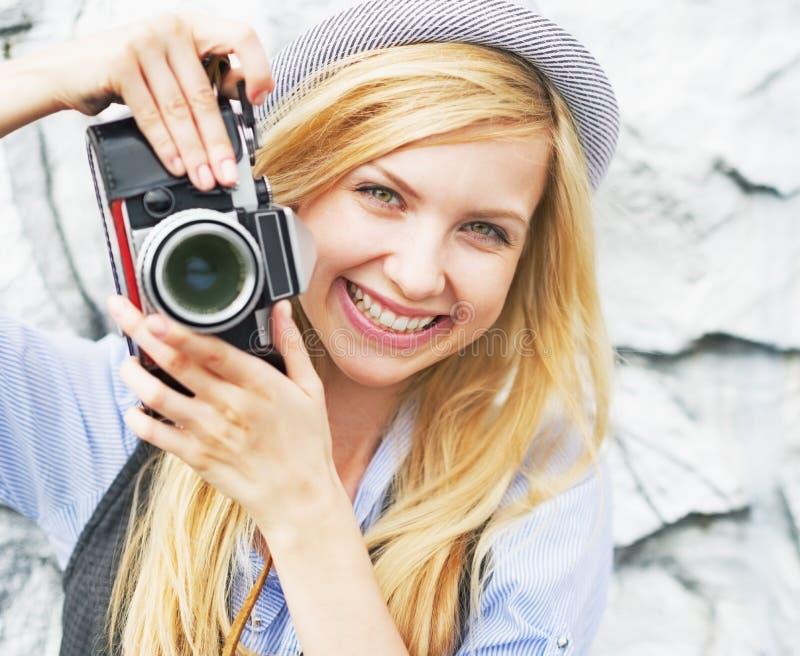 Πορτρέτο του χαμογελώντας hipster κοριτσιού που κάνει τη φωτογραφία με την αναδρομική κάμερα στοκ φωτογραφία με δικαίωμα ελεύθερης χρήσης