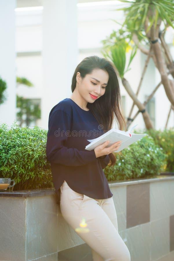 Πορτρέτο του χαμόγελου του βιβλίου ανάγνωσης γυναικών σπουδαστών στεμένος υπαίθριος στο πεζούλι του καφέ πανεπιστημιουπόλεων στην στοκ εικόνες με δικαίωμα ελεύθερης χρήσης