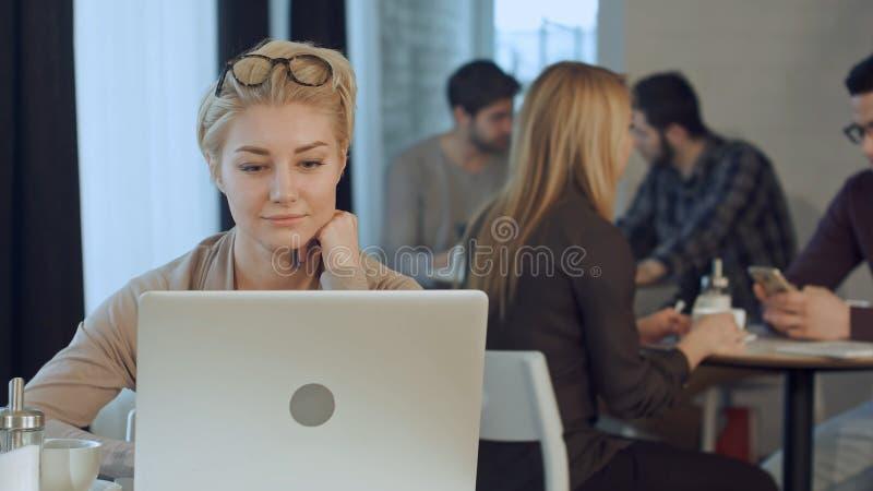 Πορτρέτο του χαμόγελου της αρκετά νέας επιχειρησιακής γυναίκας που αναβάλλει τα γυαλιά που κάθονται στο lap-top καφέδων woth στοκ εικόνες με δικαίωμα ελεύθερης χρήσης