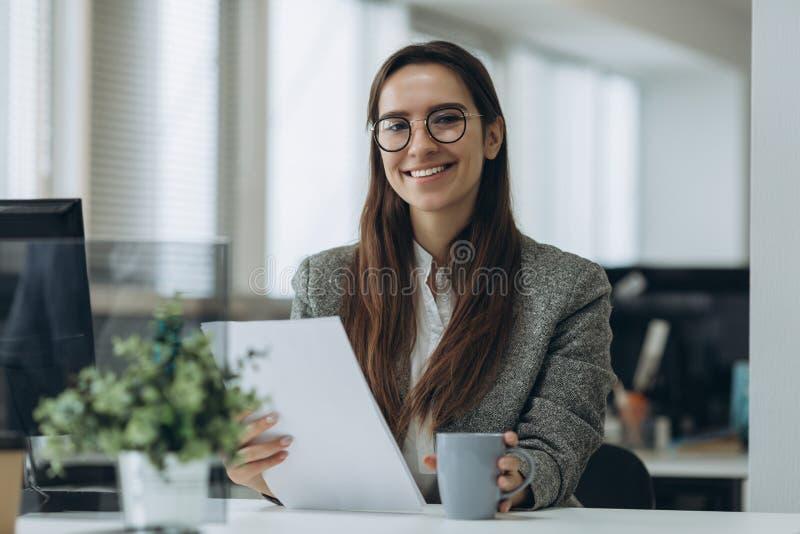 Πορτρέτο του χαμόγελου της αρκετά νέας επιχειρησιακής γυναίκας στα γυ στοκ φωτογραφία