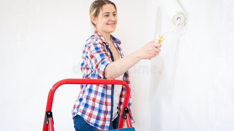 Πορτρέτο του χαμόγελου των όμορφων τοίχων ζωγραφικής κοριτσιών με τον κύλινδρο χρωμάτων στοκ φωτογραφία με δικαίωμα ελεύθερης χρήσης