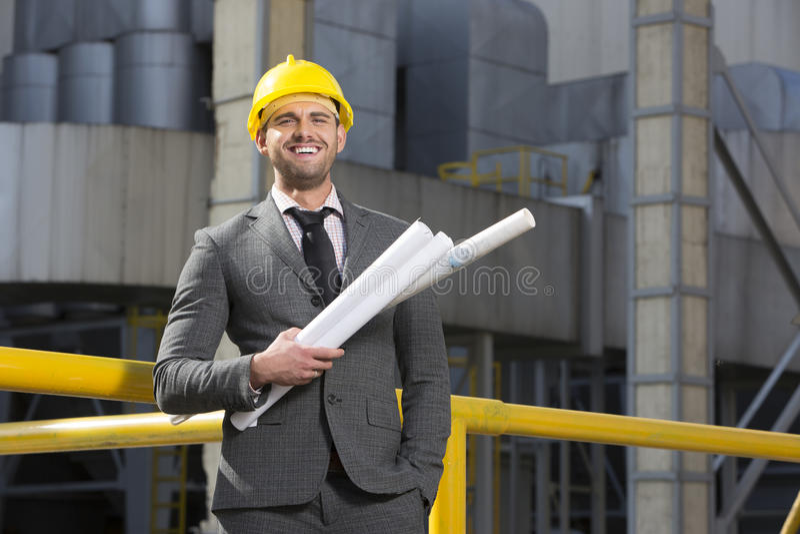 Πορτρέτο του χαμόγελου των νέων αρσενικών σχεδιαγραμμάτων εκμετάλλευσης αρχιτεκτόνων έξω από την οικοδόμηση στοκ φωτογραφία
