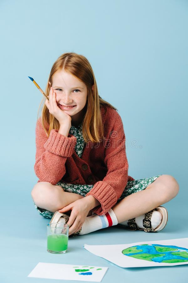 Πορτρέτο του χαριτωμένου έφηβη που μετά από να χρωματίσει τον πλανήτη σε χαρτί στοκ εικόνες με δικαίωμα ελεύθερης χρήσης