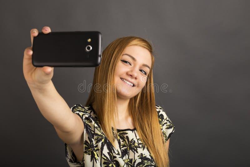Πορτρέτο του χαριτωμένου έφηβη που παίρνει selfie με το έξυπνο τηλέφωνό της στοκ φωτογραφίες με δικαίωμα ελεύθερης χρήσης