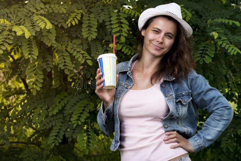 Πορτρέτο του χαριτωμένου ελκυστικού κοριτσιού στο καπέλο με το ποτήρι του κρύου ποτού με το άχυρο στη φύση πάρκων στοκ εικόνες με δικαίωμα ελεύθερης χρήσης