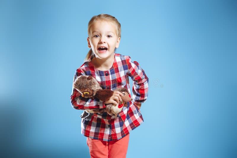 Πορτρέτο του χαριτωμένου μικρού κοριτσιού με τα παιχνίδια στο μπλε υπόβαθρο στοκ εικόνες