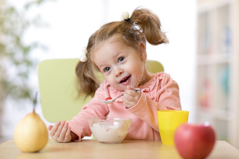 Πορτρέτο του χαριτωμένου μικρού κοριτσιού που τρώει τα φρούτα και το γιαούρτι για το πρόγευμα στο σπίτι στοκ εικόνα