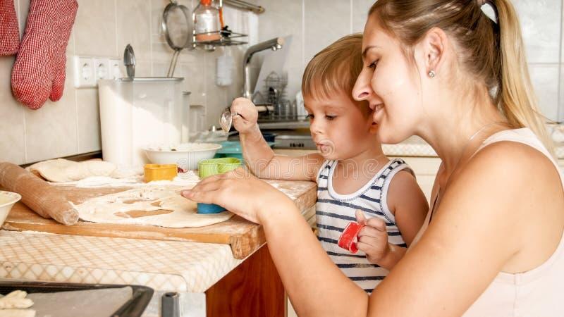 Πορτρέτο του χαριτωμένου μικρού παιδιού με τα νέα μπισκότα ψησίματος μητέρων στο τηγάνι ψησίματος στην κουζίνα στοκ φωτογραφία