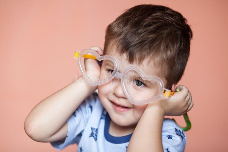 Πορτρέτο του χαριτωμένου μικρού παιδιού που φορά διαμορφωμένα τα καρδιά γυαλιά στοκ εικόνες