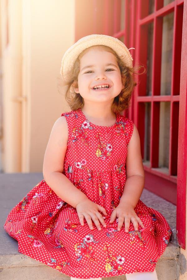 Πορτρέτο του χαριτωμένου ξανθού κοριτσιού στην τοποθέτηση ιματισμού στην ηλιόλουστη ημέρα και την εξέταση τη κάμερα υπαίθρια στοκ φωτογραφία