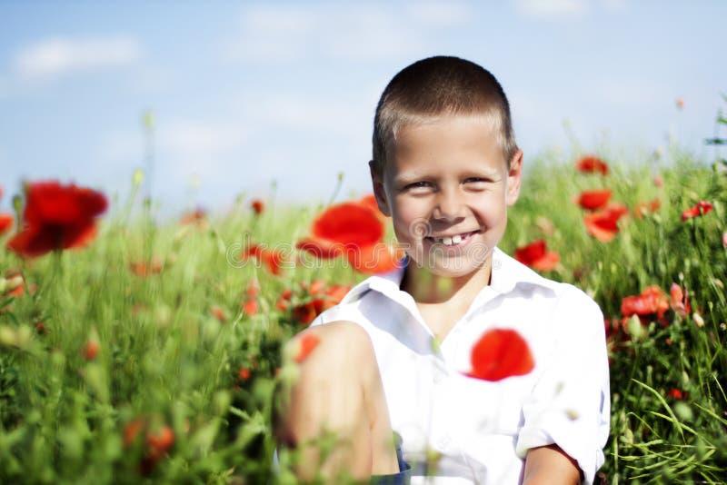 Πορτρέτο του χαριτωμένου χαμογελώντας αγοριού στο πεδίο παπαρουνών στοκ εικόνα με δικαίωμα ελεύθερης χρήσης
