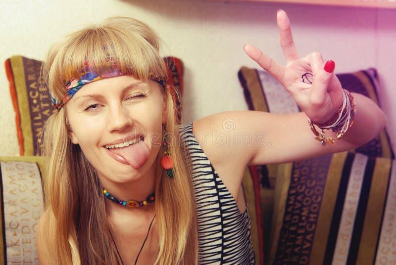 Πορτρέτο του χαρούμενου κοριτσιού hipster που κάνει το αστείο πρόσωπο, που παρουσιάζει tong στοκ εικόνες