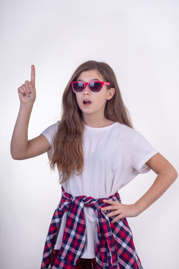Πορτρέτο του χαρούμενου νέου κοριτσιού με τα γυαλιά ηλίου που θέτουν και που δείχνουν το δάχτυλο σε ελεύθερου χώρου για τη διαφήμ στοκ εικόνες