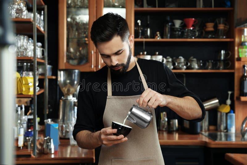 Πορτρέτο του χύνοντας γάλακτος barista στο φλιτζάνι του καφέ ενάντια στα ράφια φραγμών στοκ φωτογραφία