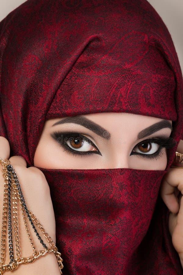 Πορτρέτο του όμορφου αραβικού κοριτσιού που κρύβει το πρόσωπό της στοκ φωτογραφία