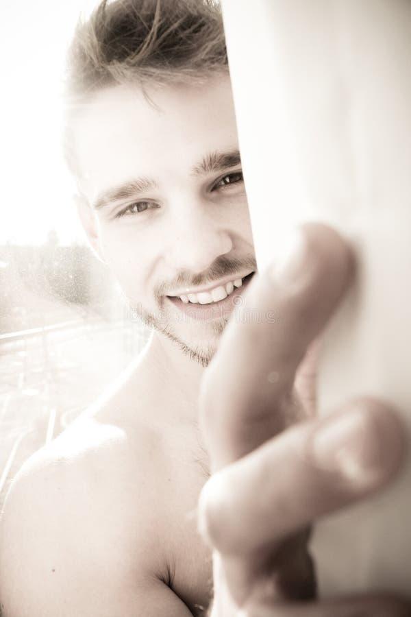 Πορτρέτο του όμορφου ατόμου αναμμένου από την ηλιοφάνεια μέσω του παραθύρου που κρυφοκοιτάζει έξω από την πίσω κουρτίνα στοκ φωτογραφία