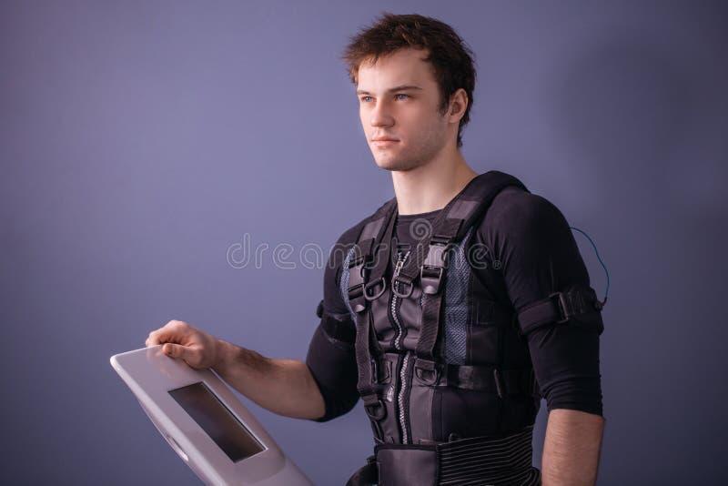 Πορτρέτο του όμορφου ατόμου κοντά στην ηλεκτρο μηχανή υποκίνησης μυών στοκ εικόνες