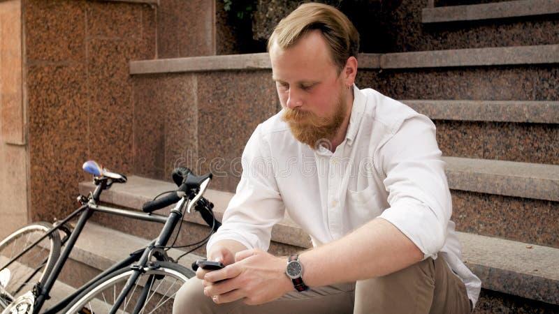 Πορτρέτο του όμορφου ατόμου με την κόκκινη συνεδρίαση γενειάδων στα σκαλοπάτια στην οδό και τη χρησιμοποίηση του smartphone στοκ φωτογραφίες με δικαίωμα ελεύθερης χρήσης