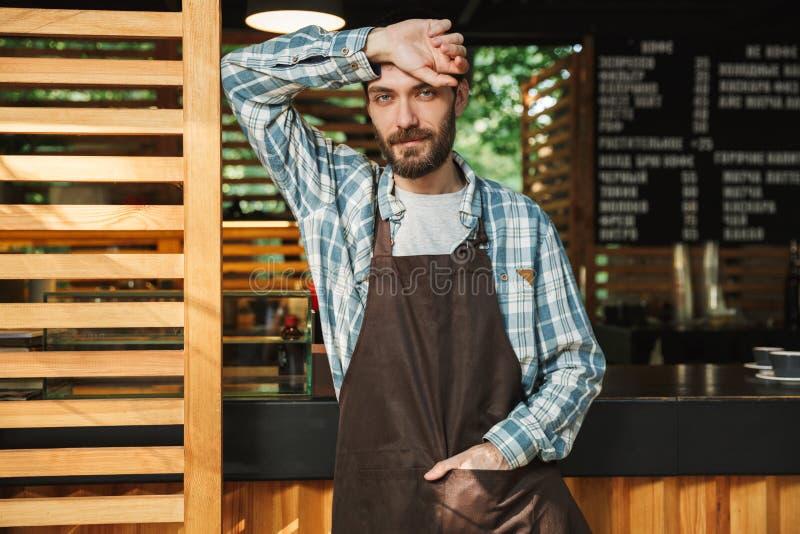 Πορτρέτο του όμορφου ατόμου barista που λειτουργεί στον καφέ οδών ή του καφέ υπαίθριου στοκ εικόνα