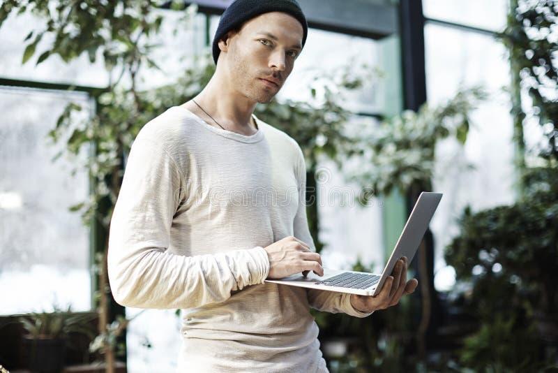Πορτρέτο του όμορφου ατόμου hipster που εργάζεται στο φορητό προσωπικό υπολογιστή υπαίθριο στο πάρκο χρυσή ιδιοκτησία βασικών πλή στοκ φωτογραφίες