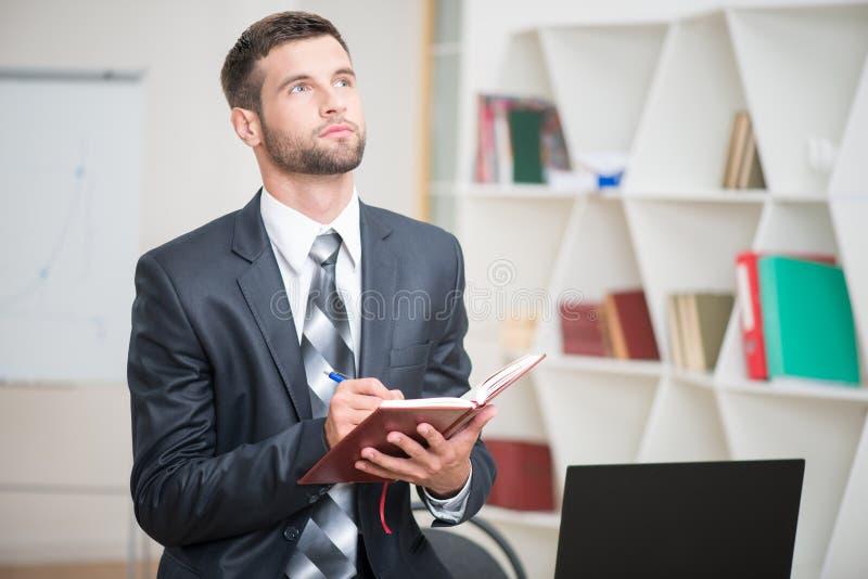Πορτρέτο του όμορφου βέβαιου γραψίματος επιχειρηματιών στοκ φωτογραφία