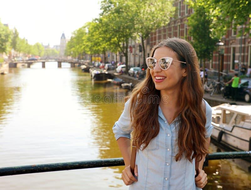 Πορτρέτο του όμορφου εύθυμου κοριτσιού με τα γυαλιά ηλίου που κοιτάζει στην πλευρά σε ένα από τα χαρακτηριστικά κανάλια του Άμστε στοκ φωτογραφία