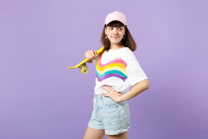Πορτρέτο του όμορφου κοριτσιού εφήβων στα ζωηρά ενδύματα που κοιτάζει κατά μέρος, που κρατά κίτρινο skateboard απομονωμένο στην ι στοκ εικόνες