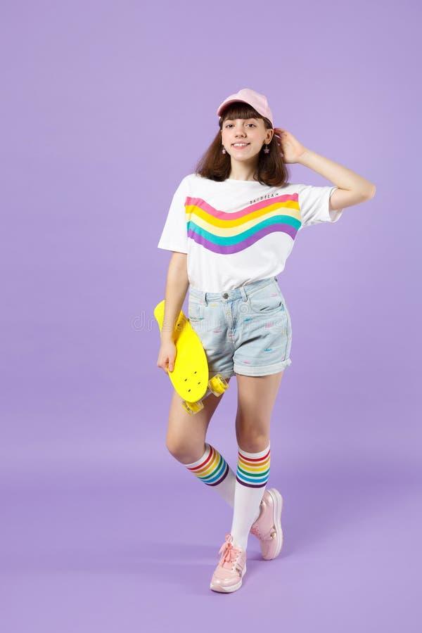 Πορτρέτο του όμορφου κοριτσιού εφήβων στα ζωηρά ενδύματα που κρατά κίτρινο skateboard, που βάζει το χέρι στο κεφάλι που απομονώνε στοκ εικόνα