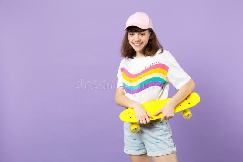 Πορτρέτο του όμορφου κοριτσιού εφήβων στα ζωηρά ενδύματα που φαίνεται κάμερα, που κρατά κίτρινο skateboard απομονωμένο στην ιώδη  στοκ εικόνα