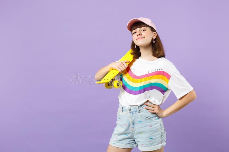 Πορτρέτο του όμορφου κοριτσιού εφήβων στα ζωηρά ενδύματα που φαίνεται κάμερα, που κρατά κίτρινο skateboard απομονωμένο στην ιώδη  στοκ εικόνα με δικαίωμα ελεύθερης χρήσης